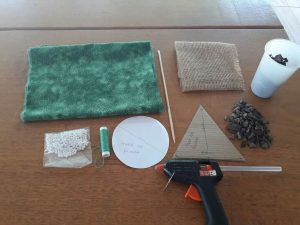Separe os materiais. Você vai precisar de tecido, cola-quente, tesoura, linha, agulha, pérolas de plástico, copo descartável, juta, pedras e um palito de churrasco
