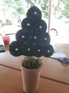 Agora, é só encaixar a árvore no copo e pronto! Para um acabamento mais bonito, tampe as pedras com musgos